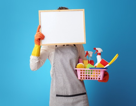 young cleaning woman in apron with a basket with detergents and brushes holding blank board in the front of face isolated on blue background. Female cleaner recommends life hacks for clean home