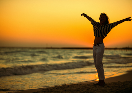 Full length portrait of modern woman on the beach at sunset rejoicing. Real freedom is only in our head! Nothing can put a desire to enjoy the sunset on the beach! Stock Photo