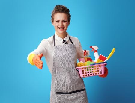 glückliche junge Putzfrau in Schürze mit einem Korb mit Reinigungsmitteln und Bürsten, die Hand für einen Handschlag einzeln auf blauem Hintergrund geben. Putzfrau begrüßt neue Kunden. Reinigungsservice