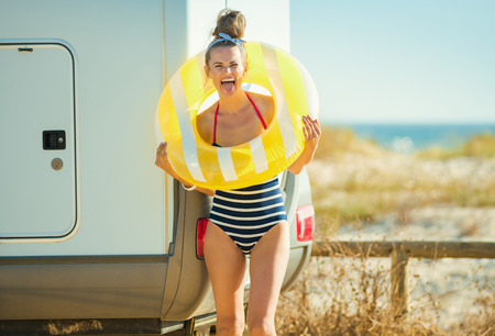 cheerful young woman in swimsuit with yellow inflatable lifebuoy near the trailer on the beach. Sometimes you need a quick and daring break from work. Fun, beach, trailer, joy! Stock Photo