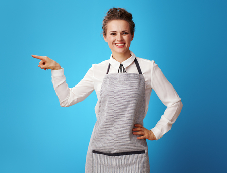 smiling young cleaning woman in apron pointing at something isolated on blue. Where to find a responsible cleaning service? The cleaning woman points to the service contacts