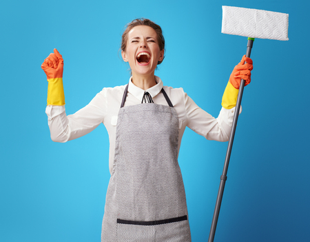 happy young cleaning woman in apron with mop rejoicing on blue background. perfect order! Here is the main goal of the cleaning woman. And thanks to customers cleaning services
