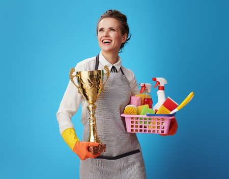 proud young scrubwoman in apron and protective orange gloves with a basket with cleansers, brushes and gold goblet looking into the distance isolated on blue