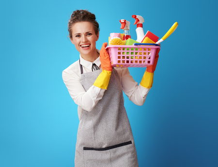 smiling young cleaning woman in apron showing a basket with detergents and brushes against blue background. Woman cleaner demonstrates environmentally friendly and organic products used in work