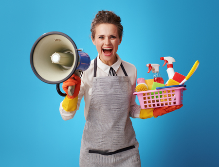 happy young cleaning lady in apron with a basket with detergents and brushes shouting through a megaphone on blue background. Emergency cleaning is not problem for a professional woman cleaner