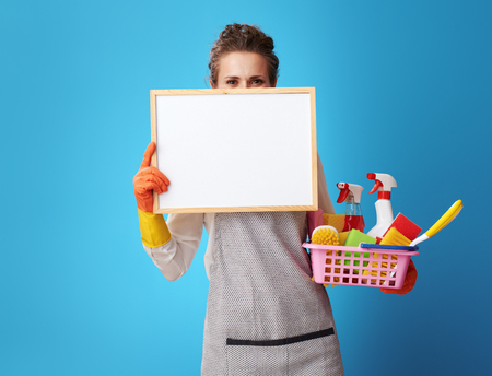 young cleaning lady in apron with a basket with detergents and brushes looking out from blank board isolated on blue background. Cleaning service worker shows the price list of cleaning prices.