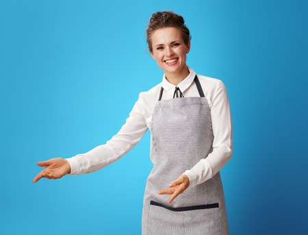 happy young housemaid in apron welcoming isolated on blue background. Housemaid invites customers to evaluate the quality of the cleaning service Banque d'images - 112759877