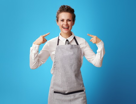 happy young cleaning lady in apron pointing at herself against blue background. The cleaning lady is a freelancer. It is worth learning to live your life.
