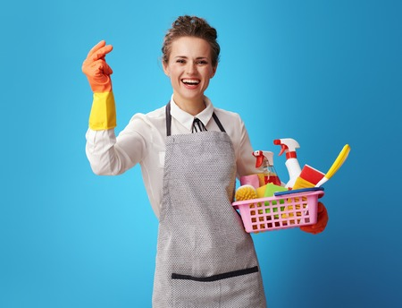 smiling housemaid in apron with basket with detergents and brushes with fingers clicking on blue background. Do not cope with cleaning the house? This is not a problem for a professional cleaner