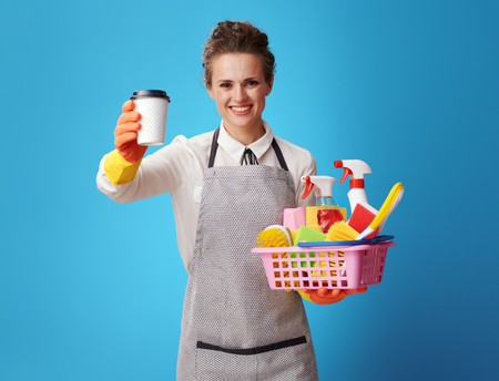 smiling young housemaid in apron with a basket with cleansers and brushes giving a coffee cup isolated on blue. Just relax with cup of coffee while professional cleaners clean up your house or office