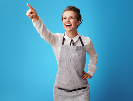 smiling young scrubwoman in apron pointing at something on blue background. Scrubwoman shows on the achievements of the cleaning service in working with customers