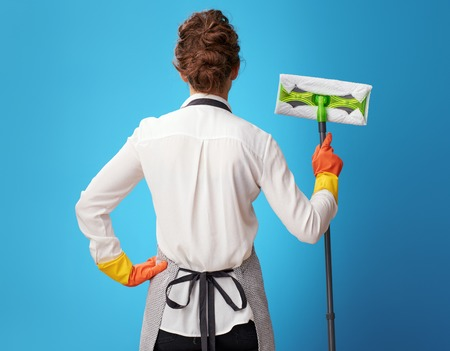 Seen from behind young cleaning lady in apron with mop isolated on blue background. Efficient, tidy, reliable and polite - the main characteristics of professional cleaning service workers Standard-Bild - 112759889
