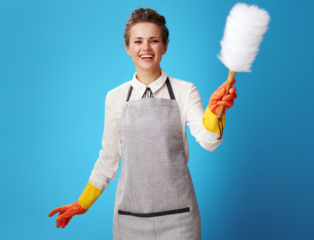 happy young housemaid in apron using dust cleaning brush against blue background. Is the customer ready to rest? So workers cleaning service ready to begin their professional duties