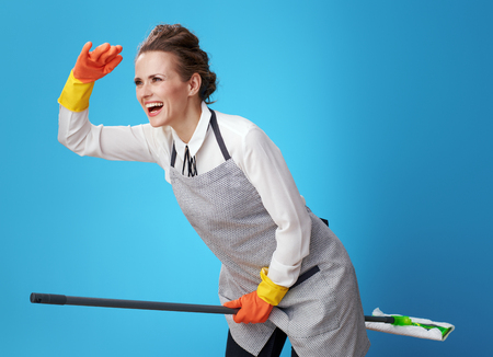 smiling young scrubwoman in apron using a mop as a broomstick against blue background. Best personalized customer service from a professional cleaning service