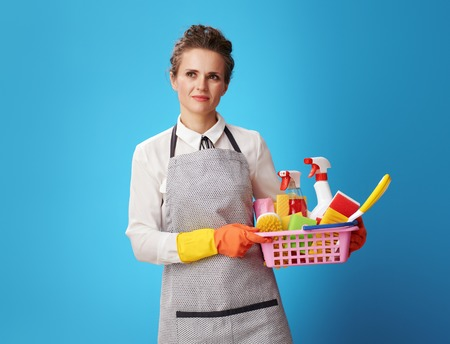 Portrait of pensive young cleaning lady in apron with a basket with detergents and brushes isolated on blue. Experienced cleaning service workers will make your home clean! Tell us what you need.