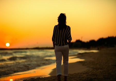 Seen from behind stylish woman on the beach in the evening walking. Stroll on the beach - a great way to get away from the busy everyday life Stockfoto