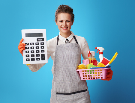smiling young housemaid in apron with a basket with cleansers and brushes showing big calculator on blue background. Do not think that cleaning service is a luxury. Calculate your time correctly 写真素材