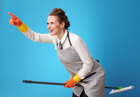 happy scrubwoman in apron pointing at something using mop as a broomstick against blue background. Is it worth spending time on tedious things? there are professional cleaning services