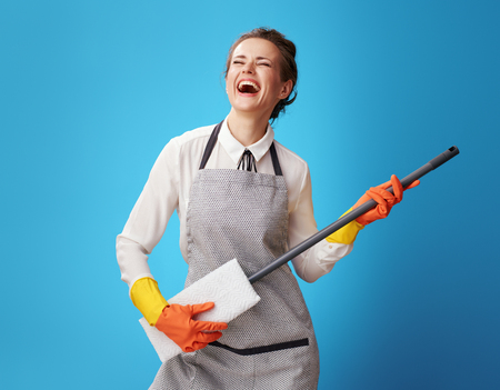 happy young cleaning woman in apron using mop as guitar isolated on blue background. The cleaning woman is enjoying the cleaning process. Strange? Everyone has their own business Stock Photo
