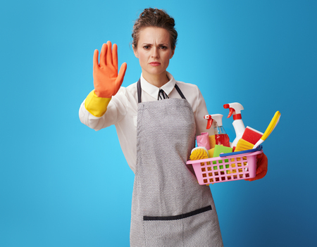 young cleaning woman in apron with a basket with cleansers and brushes showing stop gesture against blue background. Cleaning company worker warns against working with unreliable random cleaners