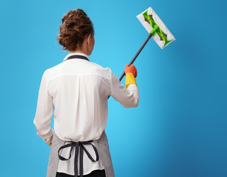 Seen from behind young cleaning woman in apron using mop on blue background. Cleaning experts always know how best to clean up your home or office