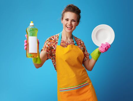 happy young housewife in orange apron with washed plate showing dishwashing liquid against blue background! Dishwashing detergent must be effective! Or you will have to forget about clean dishes.
