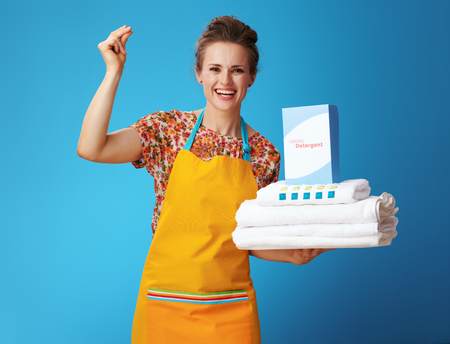 happy young woman in orange apron with white linen and powder detergent with fingers clicking isolated on blue. Millennium housewifes dream? Effective and universal cleaning powders