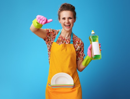 happy young housewife in orange apron with washed plate and dishwashing detergent showing thumbs up isolated on blue! Housewife demonstrates favorite dishwashing detergent Stock Photo