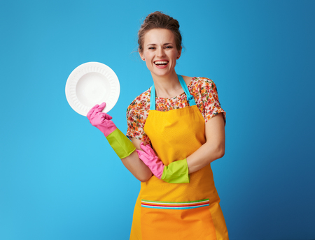 smiling young woman in orange apron showing washed plate isolated on blue. An experienced housewife is always ready to share tips on how to wash the dishes. Фото со стока