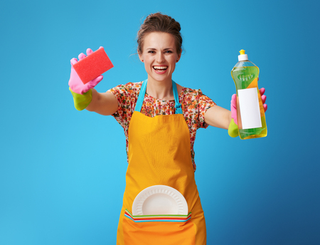 smiling woman in orange apron with washed plate showing sponge and dishwashing detergent isolated on blue background! Protective gloves, dishwashing detergent, sponge - the best help for dishwashing Stock Photo
