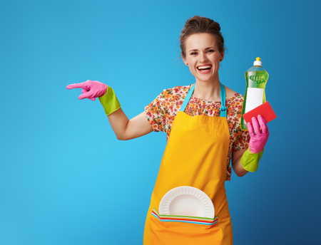 smiling young housewife in orange apron with sponge and dish soap on blue background. Environmentally friendly, effective, non-allergenic - ideal dishwashing liquid. housewife pointing on copy space
