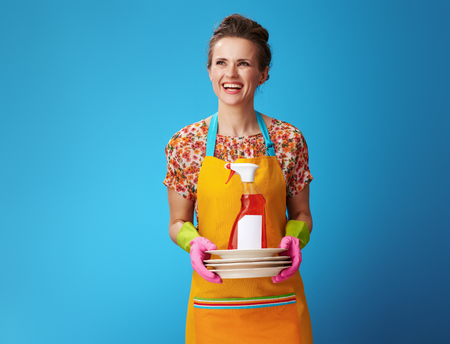happy housewife in orange apron with washed plates and dishwashing liquid looking at copy space on blue background. housewife quickly washed plates with dishwashing liquid and thought about her hobby