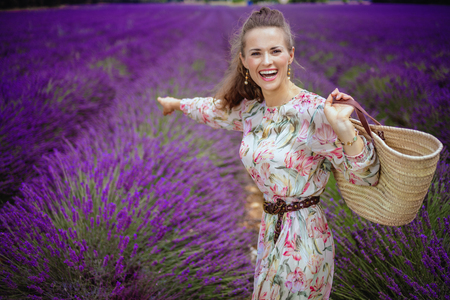 smiling elegant woman in long dress with straw bag pointing at something against lavender field of Provence, France. Provence pleases romantics with sunny landscapes and fragrant lavender fields, Stock Photo