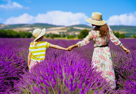 Seen from behind young mother and daughter in lavender field in Provence, France stand holding hands. Family having agritourism travel to the south of France. mother and daughter enjoying summer