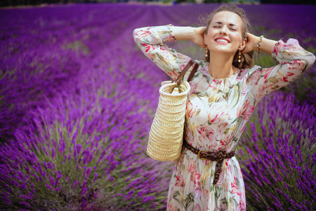 Portrait of relaxed modern woman in long dress with straw bag against lavender field of Provence, France. Woman enjoying the scent of lavender flowers