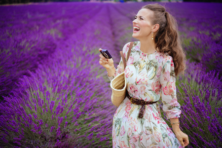happy young woman taking photo with digital camera in lavender field in Provence, France. Travel with a camera. Amazing purple lavender fields of Provence - the perfect landscape for travel photos