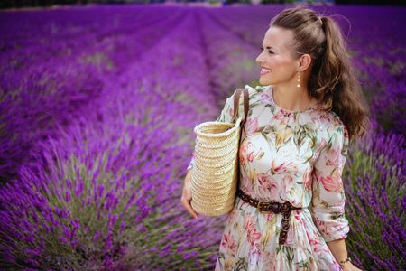 happy elegant woman with straw bag looking into the distance in lavender field in Provence, France. woman enjoying the endless fields of blooming lavender in Valensole