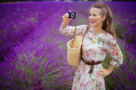 smiling elegant woman taking photo with digital camera in lavender field in Provence, France. A travel blogger in Provence takes photos for a tourist post about the lavender fields of Valensole