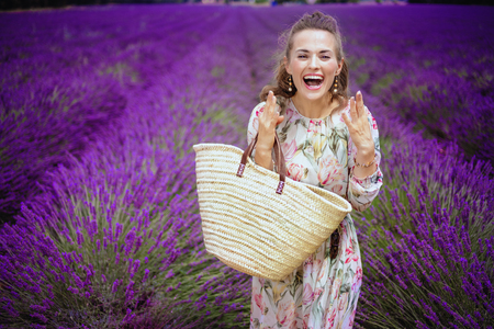 excited elegant woman with straw bag in lavender field in Provence, France. An unexpected surprise - an unplanned trip to the fragrant lavender Valensole