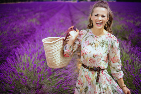 Portrait of happy stylish woman with straw bag in lavender field in Provence, France. Woman enjoying a season of flowering lavender