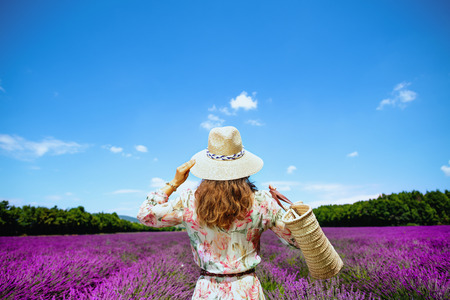 Seen from behind stylish woman in floral dress with straw bag in lavender field in Provence, France. Unforgettable adventure during summer holiday at must-see for nature lovers lavender meadows