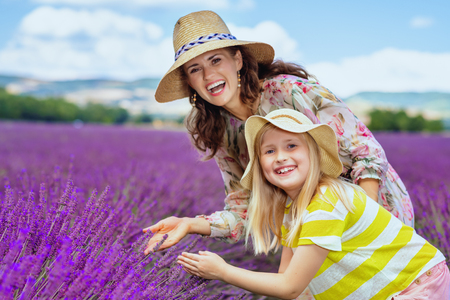 Portrait of trendy mother and child exploring lavender against lavender field of Provence, France. Perfect family agritourism with picturesque plains of lavender reveals essence of Provence