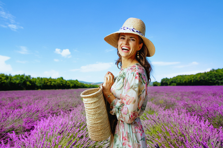 Portrait of happy young woman in summer dress with straw bag against lavender field of Provence, France. Perfect color and texture for a photo to get more likes on you social media profile