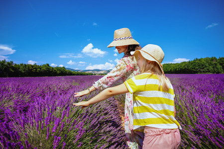 stylish mother and child in lavender field in Provence, France touching lavender. Mont Ventoux, Apt and Gordes or Luberon give you unbelievable picture-perfect landscapes. mother daughter travellers