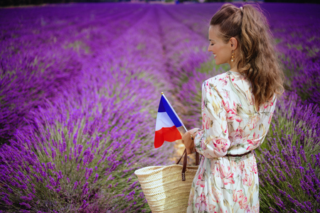 Seen from behind elegant woman in floral dress with straw bag and French flag at lavender field in Provence, France. The picturesque roads of Provence - from village of Valensole, to lavender fields