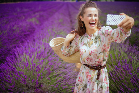happy young woman with straw bag taking selfie with cellphone in lavender field in Provence, France. Travel photos in front of background of a blooming lavender field