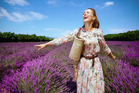 excited modern woman in summer dress with straw bag rejoicing against lavender field of Provence, France. Summer day at typical Provencal landscapes. gleeful woman traveller spending summer holidays