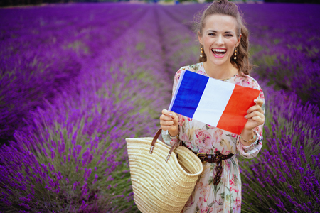smiling modern woman in long dress with straw bag showing French flag in lavender field in Provence, France. The most romantic attraction of France - blooming aromatic lavender fields of Provence Stock Photo