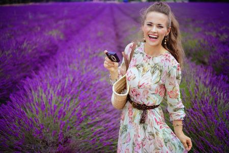 Portrait of happy elegant woman in long dress taking photo with digital camera in lavender field in Provence, France. summer in Provence -the best time to enjoy the amazing flowering lavender fields