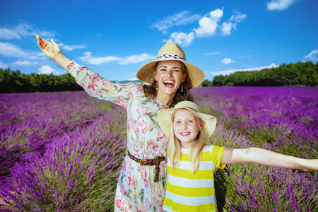 happy trendy mother and daughter in lavender field in Provence, France rejoicing. cheerful family have nice day. Day in picturescue lavender field to feel the essence of Provence. July in France
